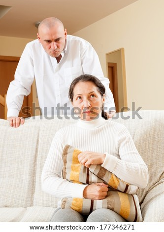 Middle-aged married couple having quarrel at home - stock photo