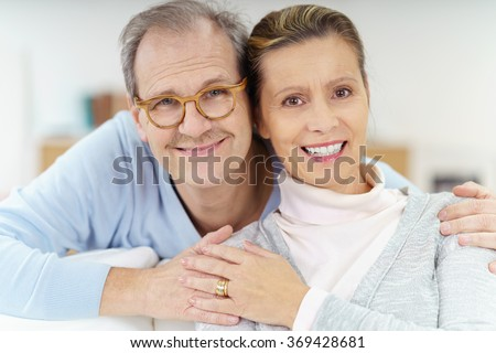 middle-aged married couple sitting on the sofa at home with his arms around her shoulders