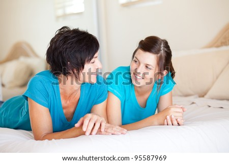 middle aged mother and teen daughter chatting on bed - stock photo