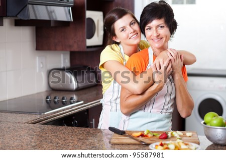 middle aged mother and teen daughter in kitchen - stock photo
