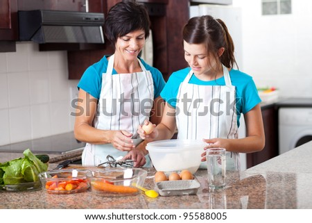middle aged mother teaching teen daughter baking in kitchen - stock photo