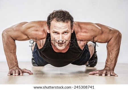 Middle-aged muscular man doing push-up - stock photo