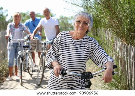 Middle-aged people on bike ride at the beach - stock photo