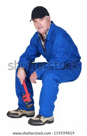 Middle-aged plumber sat down - stock photo