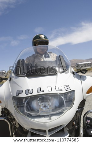 Middle aged police officer riding motorbike - stock photo