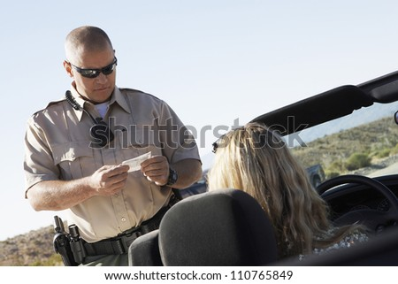 Middle aged policeman checking woman's license - stock photo