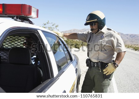 Middle aged policeman looking in car - stock photo