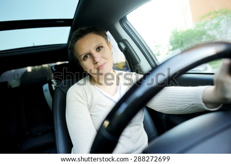 Middle aged pretty caucassian woman driving a car - stock photo