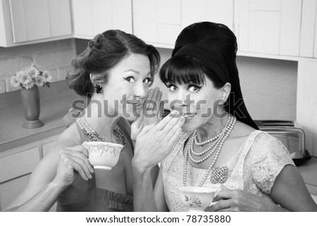 Middle-aged retro styled Caucasian woman whispers secret to her friend - stock photo