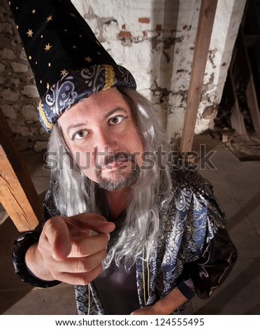 Middle aged serious European male wizard pointing - stock photo