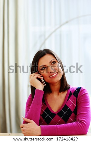 Middle-aged smiling woman talking on the phone and looking away - stock photo