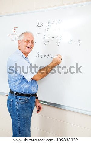Middle aged teacher or adult education student writing algebra equations on the board. - stock photo