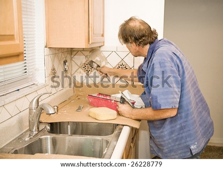 Middle aged tile-setter applying grout to kitchen tiles. - stock photo