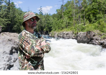 Middle aged traveler looking over the river with rapid flow. - stock photo