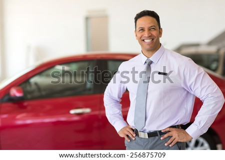 middle aged vehicle sales consultant inside showroom - stock photo