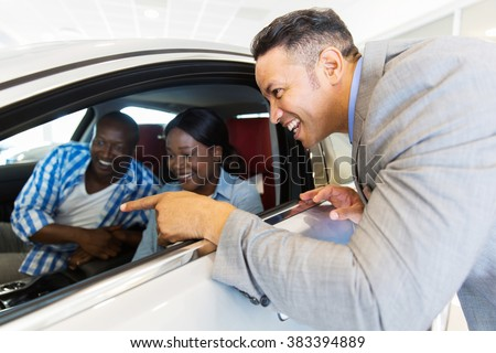 middle aged vehicle salesman showing new car to a happy young couple in showroom - stock photo