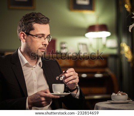 Middle-aged with cup of coffee in luxury vintage style interior  - stock photo