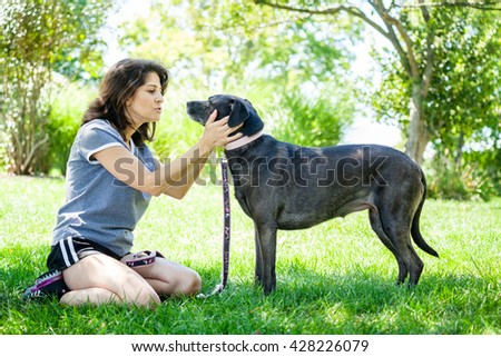Middle aged woman affectionately holding her pet labrador retriever dog looking her in the eyes at the park