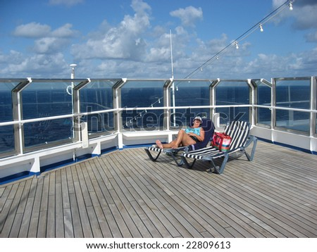 Middle-aged woman alone on the top deck of a cruise ship - stock photo