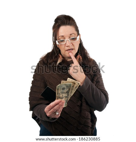 Middle aged woman carefully trying to decide between using old fashioned cash or a plastic credit or gift card.