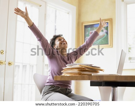 Middle-aged woman celebrating at her desk - stock photo