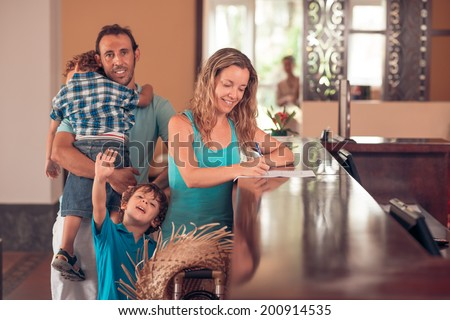 Middle-aged woman checking in, while her husband carrying a tired child, and her other son waving at the camera - stock photo