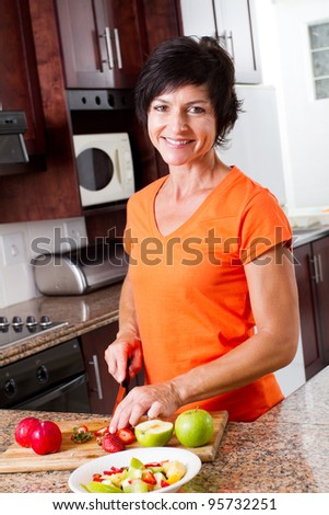 middle aged woman cooking in kitchen - stock photo