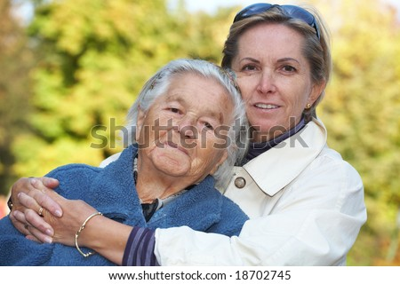Middle-aged woman cuddles her elderly mother - stock photo