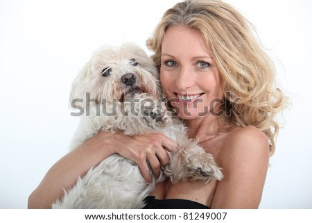Middle-aged woman cuddling dog. - stock photo