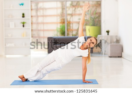 middle aged woman doing fitness exercise at home - stock photo