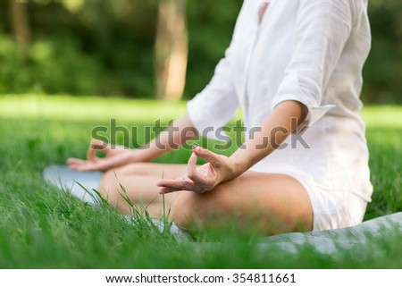 Middle aged woman doing yoga early in the morning in a park