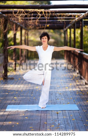 middle aged woman doing yoga pose in garden - stock photo