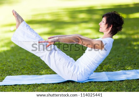 middle aged woman doing yoga pose outdoors - stock photo