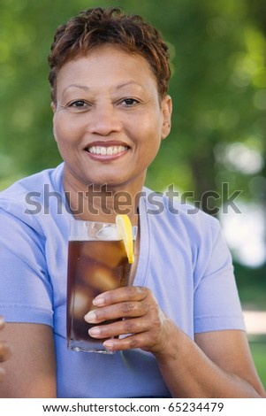 Middle-aged woman drinking a soda - stock photo