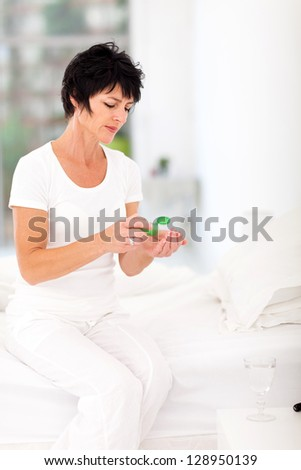 middle aged woman drinking medicine at home