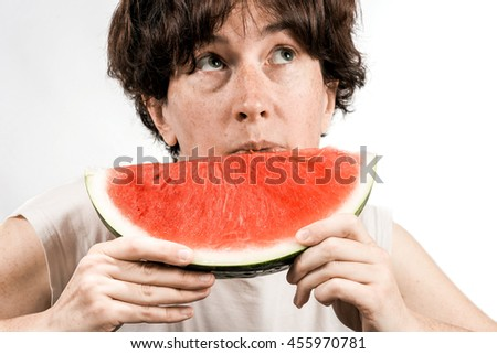 Middle-aged woman eating a piece of red melon over white background. - stock photo