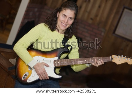 Middle aged woman electric guitar player - stock photo