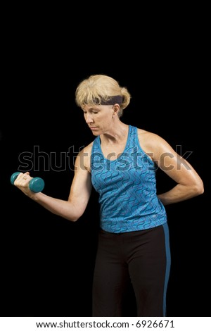 Middle-aged woman exercising doing curls with weights - stock photo