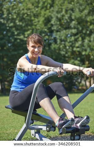 Middle Aged Woman Exercising On Rowing Machine In Park