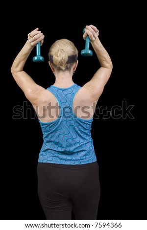Middle-aged woman exercising with weights  and with back to the camera - stock photo