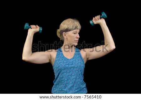 Middle-aged woman exercising with weights to music doing aerobics and enjoying it - stock photo