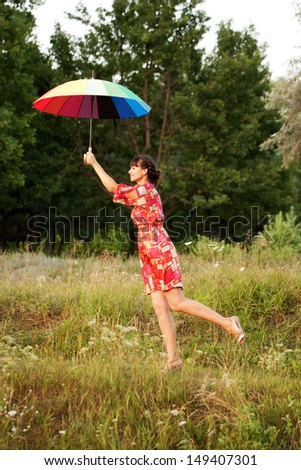 Middle-aged woman flying up with colorful umbrella