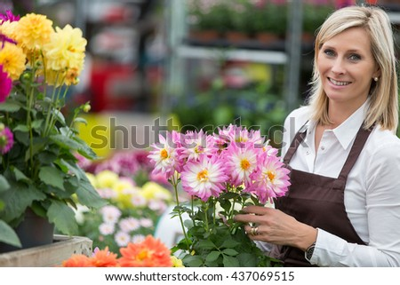middle aged woman gardening in greenhouse