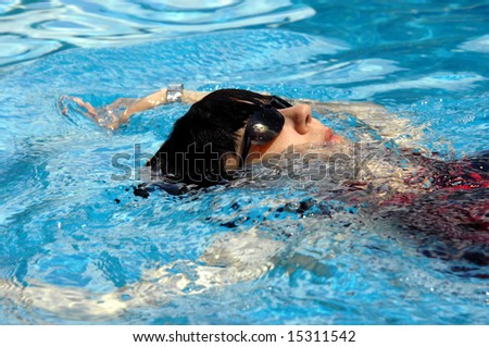 Middle aged woman gets her exercise in the swimming pool.  She is wearing sunshades and a black and red swimsuit.