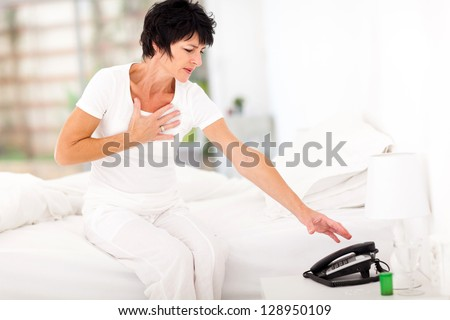 middle aged woman having heart attack and trying to reach telephone for help