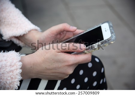 Middle-aged woman holding a cell phone - stock photo