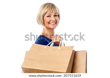 Middle aged woman holding shopping bags - stock photo