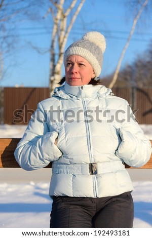 middle-aged woman in a ski jacket and a hat with pompom