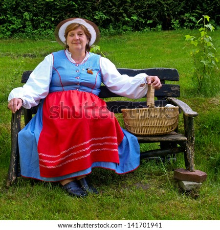 Middle-aged woman in a suit of East Prussia sitting on an old bench - stock photo