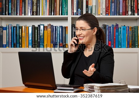 Middle aged woman in an office with her laptop, calculator and file binder talking business on the telephone, financial or tax adviser, accountant - stock photo